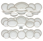 """LIMOGES - FRANCE. Aparelho de jantar com 74 peças em porcelana francesa de """"Limoges"""", manufatura """"M. Redon"""" (circa 1900), esmaltagem branca. Borda com faixa azul envolvida com guirlandas de rosas. Friso dourado. Composto de: 37 pratos rasos, 13 pratos fundos, 13 pratos de sobremesa, sopeira, par de legumeiras cobertas, 5 travessas ovais, travessa redonda, fruteira e saladeira. Reproduzido com foto no catálogo. (Em função da fragilidade, este lote só poderá ser enviado para fora do estado através de transportadora especializada)."""