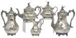 """Extraordinário aparelho para chá e café em prata inglesa do período """"Vitoriano"""", contraste da cidade de """"Sheffield"""" de 1844 a 1859. Corpo com farta ornamentação floral, lavrada e cinzelada. Pés em voluta. Puxador da tampa no feitio de pássaro. Isoladores em marfim. Composto de: bule de chá, bule de café, chocolateira, leiteira e açucareiro. Peso: 3.300g. Prateiro: """"Martin Hall & Cº Ltd"""". Reproduzido com foto no catálogo."""