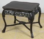"""Antiga mesinha baixa de centro em madeira escurecida, estilo oriental. Saia do tampo entalhada com dragões e flores. Pernas arqueadas com amarração em """"X"""". Pés de bicho. Alt.: 49cm. Comp.: 54cm. Prof.: 42cm."""