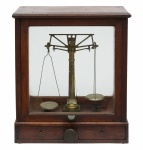 Antiga balança de precisão utilizada em farmácia ou laboratório, em metal dourado, acondicionada em caixa de madeira envidraçada com 2 gavetinhas. Acompanham pesinhos, seringas e agulhas. Alt.: 45cm. Comp.: 40cm. Prof.: 22cm. (Faltam alguns pesinhos).