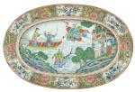 """Travessa oval em porcelana chinesa do séc. XIX, período """"Tao Kuang"""" (1821-1850), decorada no centro com """"guerreiros, carpas e figuras sobre embarcação"""". Borda com farta esmaltagem floral e pássaros. Medida: 27 X 41. Reproduzido com foto no catálogo. (Em função da fragilidade, este lote só poderá ser enviado para fora do estado através de transportadora especializada)."""