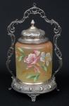 """""""Biscuit Box"""" alemão art nouveau da marca """"WMF"""" (circa 1900) em vidro opalinado esmaltado com decoração floral. Base, guarnições e tampa espessuradas a prata com decoração no estilo. Alt.: 33cm. Esta peça encontra-se reproduzida na pág. 251 do livro """"WMF"""". (Em função da fragilidade, este lote só poderá ser enviado para fora do estado através de transportadora especializada)."""