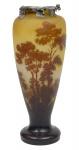 EMILLE GALLÉ (FRANÇA, 1900). Esplêndido vaso art nouveau em pasta de vidro acidado decorado com paisagem lacustre com barco e vegetação florestal nas cores branco, âmbar, verde, marrom e lilás. Borda com guarnição original em prata decorada com folhagens no estilo. Alt.: 37cm. Assinado. Reproduzido com foto no catálogo. (Em função da fragilidade, este lote só poderá ser enviado para fora do estado através de transportadora especializada).
