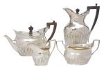 """Aparelho para chá e café em prata inglesa vitoriana contraste da Cidade de Londres de 1881. Corpo canelado. Parte superior com monograma cinzelado """"MM"""" estilizado. Pegas e puxadores em madeira. Composto de: bule de chá, bule de café, leiteira e açucareiro. Alt. do bule maior: 26cm. Peso: 1.560g. Prateiro """"Messrs Barnard""""."""